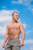 Young man against a blue sky. On a beach Stock Photos