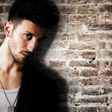 Young man against brick wall Stock Images