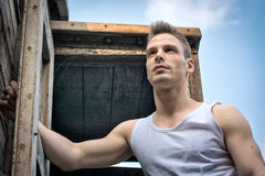 Young man against old rusty metal door and wood Royalty Free Stock Images