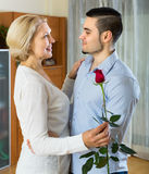 Young man and aged woman dancing indoor Stock Image