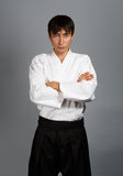 Young man in aikido uniform in serious pose Stock Photography