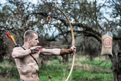 A young man aiming a bow at a target Royalty Free Stock Photos