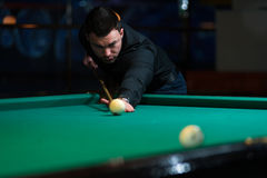 Young man aiming to take snooker shot in dark club. Playing billiard - young man aiming to take snooker shot in dark club royalty free stock photos