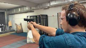 Young man aims, holding a gun at a shooting gallery, shooting range. Slow motion. Mid shot stock footage