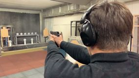 Young man aims, holding a gun at a shooting gallery, shooting range. Mid shot stock video footage