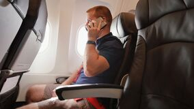 A young man in an airplane before a flight communicates on a mobile phone. A young man in an airplane before a flight communicates on a mobile phone stock video footage