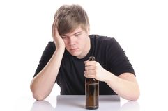 Young man alcohol abuse. Young man with short blond hair and a black T-shirt sits at a table and holding an empty beer bottle in his hand, isolated against a Stock Photography