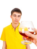Young Man with Alcohol. Hesitant Young Man with Alcohol Isolated on the White Background Royalty Free Stock Image