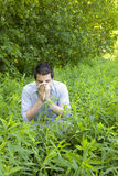 Young Man with Allergies in Field. A young man with allergies amongst weeds in a field with trees behind him stock photo