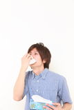 Young man with a allergy sneezing into tissue Stock Photography