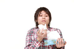 Young man with an allergy sneezing into tissue Stock Photos