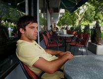 Young Man Alone In The Caffe. Beautiful young man sitting alone in the small cafe Royalty Free Stock Images