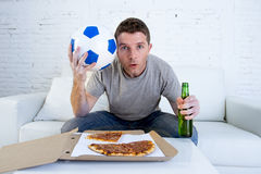 Young man alone holding ball and beer bottle watching football game on television at home sofa couch Royalty Free Stock Photography