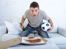 Young man alone holding ball and beer bottle watching football game on television at home sofa couch Stock Images