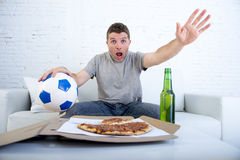 Young man alone holding ball and beer bottle watching football game on television at home sofa couch Stock Image