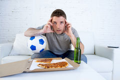 Young man alone holding ball and beer bottle watching football game on television at home sofa couch Stock Photos