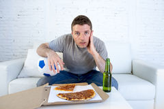 Young man alone holding ball and beer bottle watching football game on television at home sofa couch Royalty Free Stock Image
