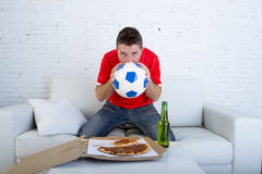 Young man alone holding ball and kissing it in stress wearing team jersey watching football tv Royalty Free Stock Photography
