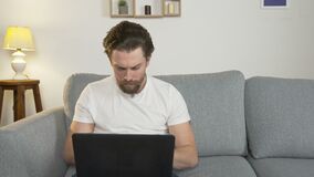 Young man alone sitting at home on the couch, on his laptop, looking for a work online, isolated from society due to
