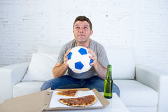 Young man alone in stress watching football game on television praying nervous and excited Royalty Free Stock Images