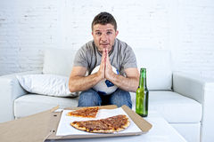 Young man alone in stress watching football game on television praying nervous and excited Stock Images