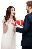 Young man amazes his girlfriend with present Royalty Free Stock Photos