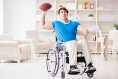The young man american football player recovering on wheelchair Stock Photos