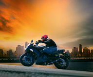 Young Man And Safety Suit Riding Big Motorcycle Against Beautiful Dusky Sky And Urban Scene With Copy Space Stock Images