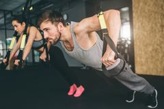 Young Man And Woman Are Doing TRX Chest Press Exercise. He Is Doing Push Up While She Is Doing Oush Down. Close Up. Cut Royalty Free Stock Photo