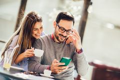 Free Young Man And Woman Dating And Spending Time Together In Cafe, Using Phone Royalty Free Stock Photography - 144412507