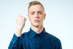 Young man angry gesturing fist raised. On isolated white background Stock Photography