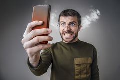 Steaming with rage, man yelling at his phone. Young man angry with his cell phone, yelling at it, letting off steam and burning his phone with rage Stock Photography