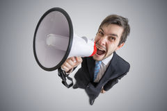 Young man is announcing a message with megaphone. View from above Royalty Free Stock Photos