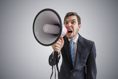 Young man is announcing a message and shouting to megaphone Stock Photography
