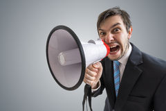 Young man is announcing a message and shouting to megaphone Royalty Free Stock Photography