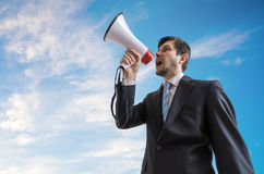 Young man is announcing a message and speaking to megaphone. Sky in background.  Royalty Free Stock Image