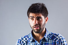 Young man with anxiety expression. Funny young man with anxiety expression - isolated on grey Royalty Free Stock Photo