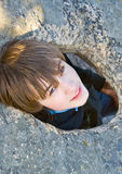 Young man in an aperture in  stone on  nature Royalty Free Stock Images