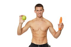 Young man with apple and carrot Royalty Free Stock Photo