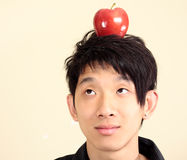Young man with an apple on his head Stock Images