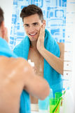 Young man applying aftershave Royalty Free Stock Image