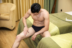 Young man applying body lotion to legs Stock Photo