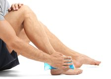 Young man applying cold compress to leg. On white background royalty free stock images