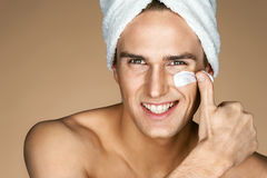 Young man applying cream to his face. royalty free stock image