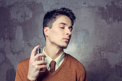 Young man applying fragrance Royalty Free Stock Photography