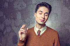 Young man applying fragrance Royalty Free Stock Photo