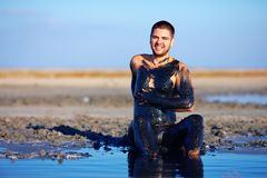 Young man applying healing clay outdoors. Young man applying black healing clay outdoors royalty free stock photo
