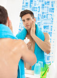 Young man applying after shave Stock Images
