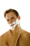 Young man applying shaving cream to his face Stock Photography