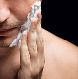 Young man applying a shaving foam royalty free stock image